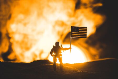 Photo for toy soldier silhouette with american flag on planet with sun in smoke - Royalty Free Image