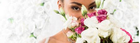 Photo pour panoramic shot of african american bride covering face with flowers - image libre de droit