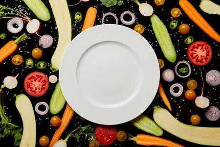 top view of empty round plate on vegetable pattern background isolated on blackの写真素材