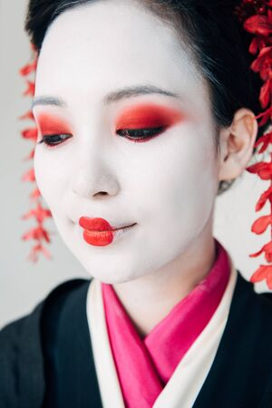 Photo pour close up view of smiling beautiful geisha in black kimono with red flowers in hair isolated on white - image libre de droit