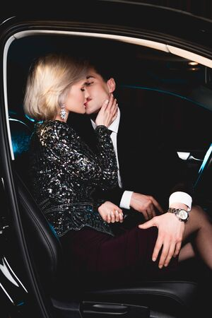Foto de stylish man kissing beautiful sensual young woman in car - Imagen libre de derechos
