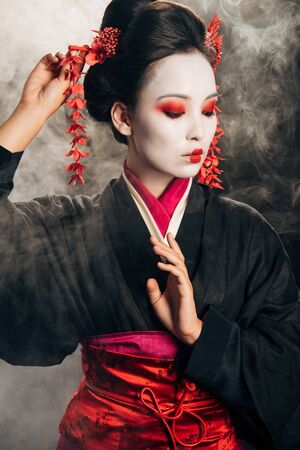 Photo for geisha in black kimono with red flowers in hair gesturing on black background with smoke - Royalty Free Image
