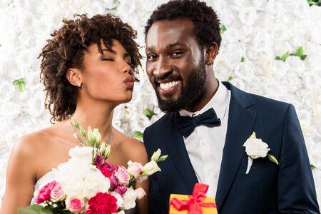 Foto für african american bride with duck face holding bouquet with flowers near cheerful bridegroom - Lizenzfreies Bild