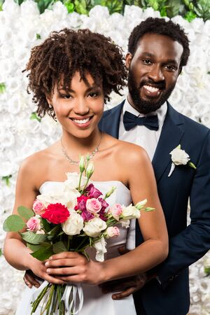 Photo pour cheerful african american bride holding bouquet with flowers near bridegroom - image libre de droit