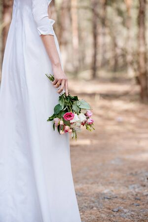 Photo for cropped view of bride in white attire holding wedding bouquet in forest - Royalty Free Image