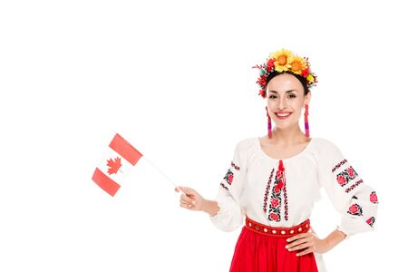 Photo pour brunette young woman in national Ukrainian costume holding flag of Canada isolated on white - image libre de droit