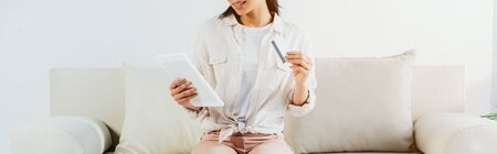 Photo pour cropped shot of latin woman holding credit card and using digital tablet while sitting on sofa - image libre de droit