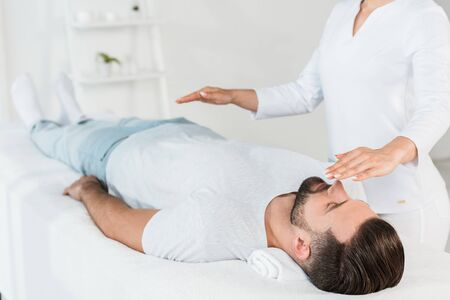 Photo for cropped view of healer with hands above body of man resting on massage table - Royalty Free Image