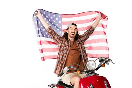Photo pour excited young man sitting on red scooter and holding American flag on air isolated on white - image libre de droit