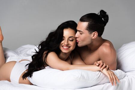 Foto de sexy undressed couple smiling while lying on bed together - Imagen libre de derechos