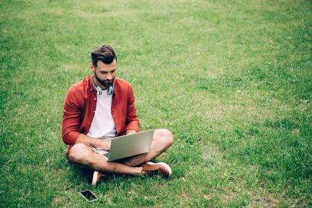 Foto de man sitting on grass in park near smartphone and using laptop - Imagen libre de derechos