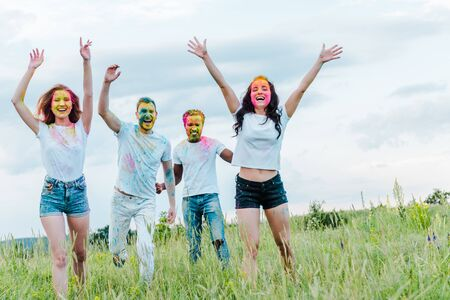 Photo for happy multicultural friends with colorful holi paints on faces gesturing while standing outside - Royalty Free Image