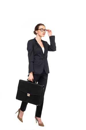 Photo pour full length view of successful businesswoman in black suit and glasses with briefcase isolated on white - image libre de droit