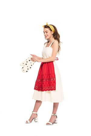 Photo pour full length view of young happy housewife in dress and apron holding oven mitten isolated on white - image libre de droit