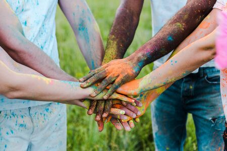 Photo for cropped view of multicultural friends with colorful holi paints putting hands together - Royalty Free Image