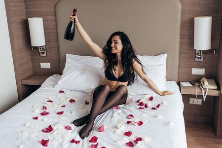 Foto de sexy brunette girl in black lingerie sitting on bed covered with rose petals and holding bottle of champagne with smile in bedroom - Imagen libre de derechos
