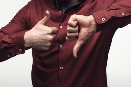 Foto de partial view of man showing thumb up and thumb down isolated on grey, human emotion and expression concept - Imagen libre de derechos