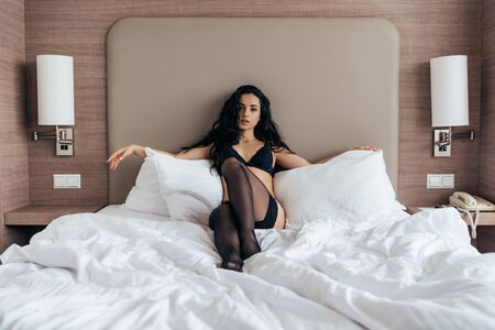 Photo for front view of sexy brunette girl in black stockings and underwear lying in bed - Royalty Free Image