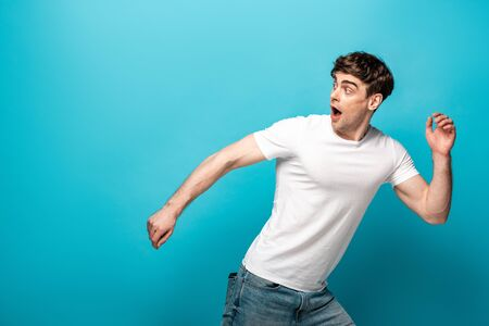 Photo pour scared young man running away and looking back on blue background - image libre de droit