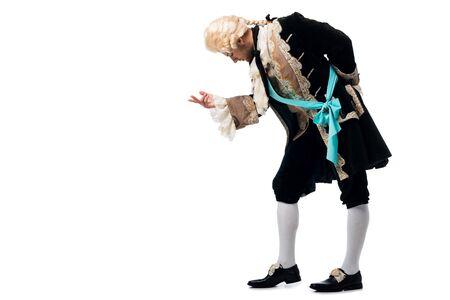 Foto de handsome victorian gentleman in wig gesturing while bowing down isolated on white - Imagen libre de derechos