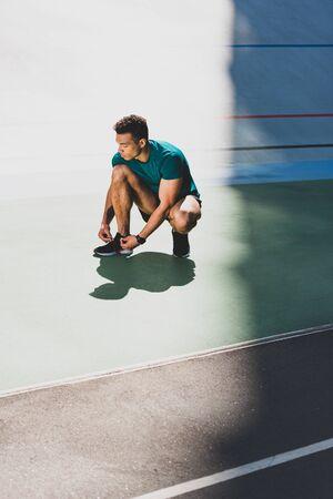 Foto de mixed race sportsman lacing up sneakers at stadium - Imagen libre de derechos