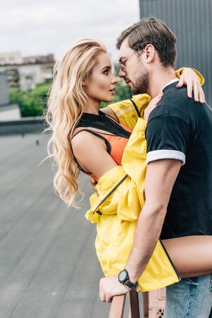 Photo pour blonde woman and handsome man hugging and looking at each other - image libre de droit