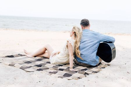 Photo pour back view of young blonde barefoot woman sitting on checkered blanket near boyfriend with acoustic guitar at beach near sea - image libre de droit