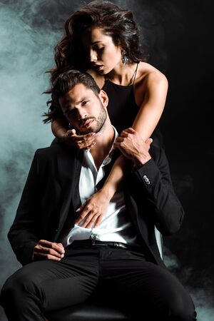 Foto de passionate girl standing and hugging handsome bearded man on black with smoke - Imagen libre de derechos