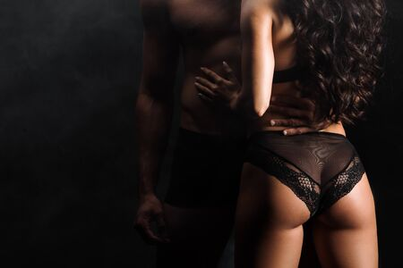 Foto de cropped view of man standing with sexy woman on black with smoke - Imagen libre de derechos