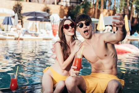 Photo for excited young couple taking selfie while sitting at poolside with glasses of refreshing beverage - Royalty Free Image
