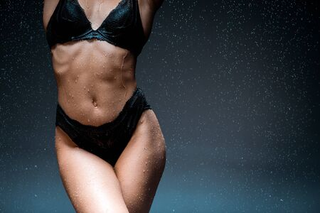 Photo pour cropped view of young woman standing in underwear under raindrops on black - image libre de droit