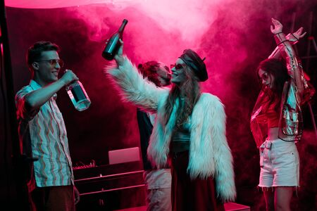 Photo pour men and girls with alcohol dancing in nightclub with pink smoke - image libre de droit