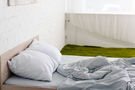 Photo pour Wooden bed with pillows and crumpled light blanket in white room with green carpet - image libre de droit