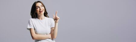 Photo for happy beautiful girl in white t-shirt showing idea gesture and looking away isolated on grey, panoramic shot - Royalty Free Image
