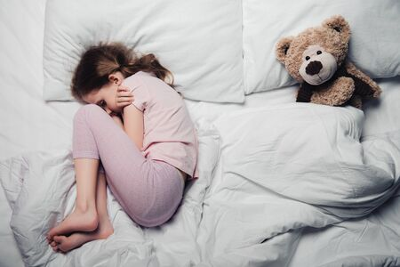 Photo pour top view of scared child lying on white bedding near teddy bear - image libre de droit