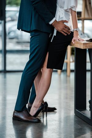 Photo pour cropped view of businessman standing and touching businesswoman while flirting in office - image libre de droit
