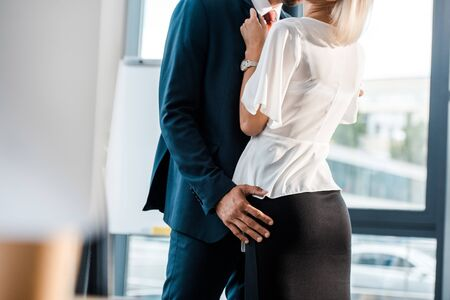 Photo pour cropped view of businessman touching buttocks of coworker in office - image libre de droit