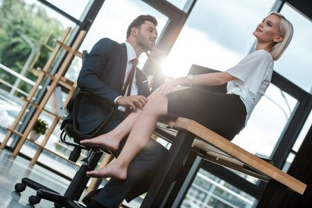 Photo for handsome bearded man looking at attractive girl sitting on table in office - Royalty Free Image
