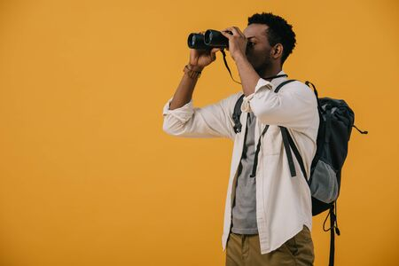 Photo pour african american man looking through binoculars isolated on orange - image libre de droit