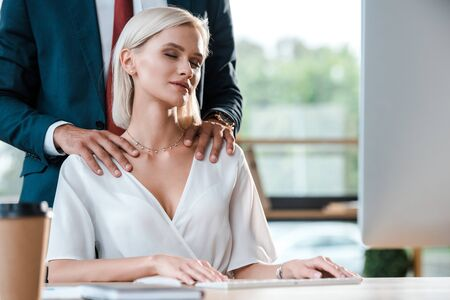 Photo pour cropped view of businessman in suit touching attractive blonde woman with closed eyes - image libre de droit