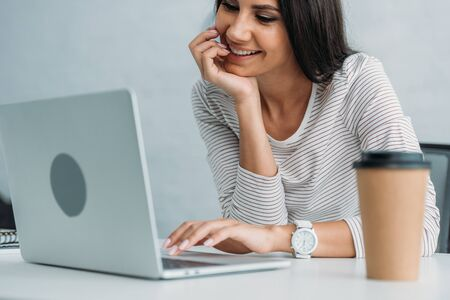 Foto de attractive and brunette woman smiling and using laptop in apartment - Imagen libre de derechos
