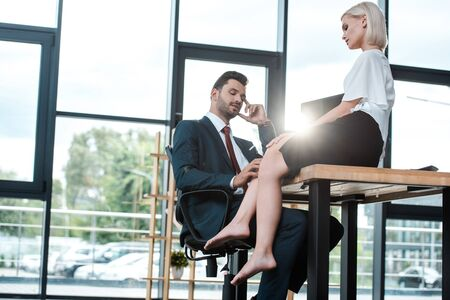 Photo pour handsome man touching leg of attractive woman sitting on table in office - image libre de droit