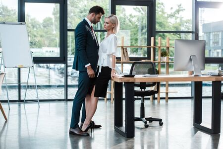 Photo pour handsome businessman touching attractive young woman while flirting in office - image libre de droit