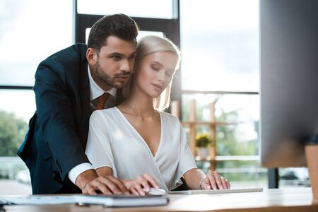 Photo pour selective focus of bearded businessman in suit standing near attractive blonde girl in office - image libre de droit