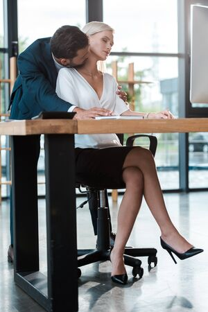 Photo pour bearded businessman kissing neck of attractive blonde woman with closed eyes - image libre de droit