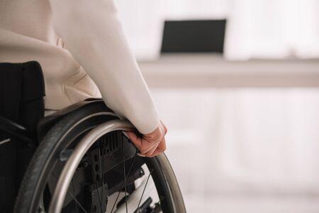 Photo pour disabled businesswoman sitting in wheelchair near desk with laptop - image libre de droit