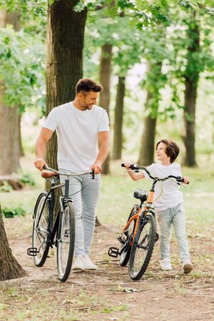 Photo pour full length view of happy father and son looking at each other and smiling while walking with bicycles in forest - image libre de droit