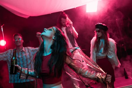 Photo pour girl holding beer and dancing in nightclub with pink smoke - image libre de droit