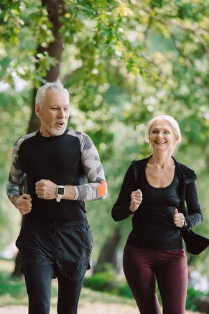 Foto für cheerful mature sportsman and sportswoman running together in park - Lizenzfreies Bild