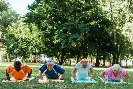 Photo pour sportive retired and multicultural men and woman exercising on fitness mats - image libre de droit
